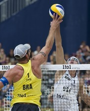 Brasil's Alison Cerutti, left, blocks a ball against US Jake Gibb, right, during the final game at the Beachvolley Worldtour in Gstaad, Switzerland, Sunday, July 8, 2012. The US team won the match. (AP Photo/Keystone/Peter Schneider)