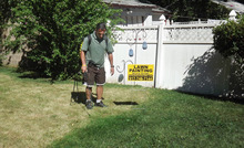 This July 25, 2012 photo provided by Grass is Greener Lawn Painting shows the company's owner, Joseph Perazzo, working on a lawn in Irvington, N.J. With drought spanning about two-thirds of the nation from California to New York, some residents and businesses in normally well-watered areas are taking a page from the lawn-painting practices employed for years in the West and South to give luster to faded turf. (AP Photo/Grass is Greener Lawn Painting)