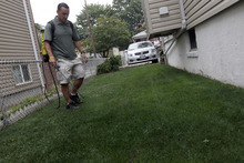 Joseph Perazzo, owner of Grass is Greener Lawn Painting, demonstrates how he spays lawns at a house on the Staten Island borough of New York, Thursday, July 26, 2012.  When this summer's nationwide drought turned her prized lawn brown, Terri LoPrimo fought back in a new way: She had it painted green, making her suddenly lush-appearing yard the envy of her neighborhood. (AP Photo/Mary Altaffer)