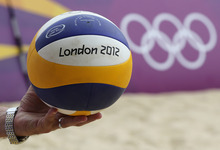 An unidentified coach holds a ball during a practice session at the Beach Volleyball venue at the 2012 Summer Olympics, Friday, July 27, 2012, in London. (AP Photo/Petr David Josek)