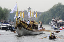 This photo provided by LOCOG shows the royal barge Gloriana carrying Olympic flame burning in the cauldron as it makes its way down the River Thames towards Richmond Bridge during the final day of the Olympic torch relay in London, Friday July 27, 2012. (AP Photo/LOCOG, Ben Birchall)
