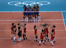 Members of the China women's volleyball team, bottom, celebrate their victory over Serbia in a preliminary match at the 2012 Summer Olympics, Saturday, July 28, 2012, in London. (AP Photo/Jeff Roberson)
