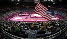 Rome Milan of Fort Worth, Texas, waves the U.S. flag during the Artistic Gymnastics men's qualification at the 2012 Summer Olympics, Saturday, July 28, 2012, in London. (AP Photo/Julie Jacobson)