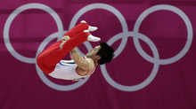 South Korean gymnast Kim Seungil performs on the parallel bars during the Artistic Gymnastic men's qualification at the 2012 Summer Olympics, Saturday, July 28, 2012, in London. (AP Photo/Julie Jacobson)