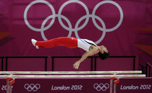 South Korean gymnast Kim Hee-hoon performs on the parallel bars during the Artistic Gymnastic men's qualification at the 2012 Summer Olympics, Saturday, July 28, 2012, in London. (AP Photo/Julie Jacobson)
