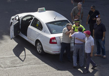 A working taxi driver grapples with a protesting taxi driver during a demonstration by taxi drivers in Madrid Friday July 27, 2012. The taxi drivers are protesting the planned deregulation of the taxi sector. (AP Photo/Paul White)