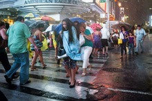 A pedestrian rushes through a torrential downpour in Times Square, Thursday, July 26, 2012, in New York. (AP Photo/John Minchillo)