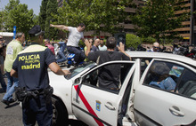 A taxi in service is attacked by other taxi drivers during a demonstration in Madrid Friday July 27, 2012. The taxi drivers are protesting the planned deregulation of the taxi sector. (AP Photo/Paul White)