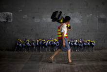 A roadworker walks past flowers placed under a bridge where a man drowned on Saturday, July 21 in his flooded car on a main road in Beijing Friday, July 27, 2012. Chinese characters on the wraps read