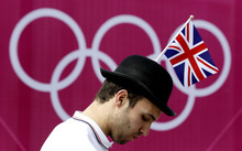 A man wears a British flag on his hat while in line to get into the Olympic Park during the 2012 Summer Olympics, Saturday, July 28, 2012, in London. (AP Photo/Julio Cortez)