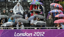 Rain pours on spectators at the Beach Volleyball venue during a beach volleyball match at the 2012 Summer Olympics, Sunday, July 29, 2012, in London. (AP Photo/Dave Martin)