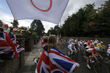 Local residents cheer as cyclists ride along the roads of Twickenham, during the Women's Road Cycling race at the 2012 Summer Olympics, Sunday, July 29, 2012, in London.  (AP Photo/Lefteris Pitarakis)
