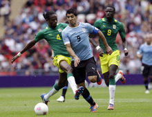 Uruguay's Luis Suarez (9) is tackled by Senegal's Abdoulaye Ba (4) as Senegal's Cheikhou Kouyate (8) watches, resulting in a red card for Ba during a men's first-round group A soccer match at the 2012 Summer Olympics, Sunday, July 29, 2012, at Wembley Stadium in London. (AP Photo/Ben Curtis)