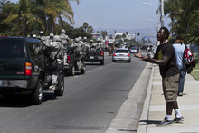 Demetrius Brown demonstrates as SUV's filled with Anaheim Police pass a block of protesters in Anaheim, Calif., Sunday, July 29, 2012. Protesters gathered in front of the Anaheim Police Department in response to two fatal police shootings last week. (AP Photo/The Los Angeles Times, Arkasha Stevenson) MANDATORY CREDIT