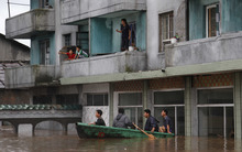 Residents wait on the balcony of a flooded building in Anju City, South Phyongan Province, North Korea Monday, July 30, 2012. More heavy rain has pounded North Korea, flooding buildings and farmland and forcing stranded people and their livestock to take shelters atop rooftops. (AP Photo/Kim Kwang Hyon)