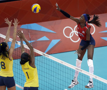 United States' Destinee Hooker, right, spikes the ball over Brazil's Jaqueline Carvalho (8) and Fabiana Claudino (1) during a women's preliminary volleyball match at the 2012 Summer Olympics, Monday, July 30, 2012, in London. (AP Photo/Jeff Roberson)