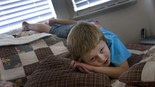Scott Sommerdorf  |  The Salt Lake Tribune              Six-year-old Logan Hilton, who is autistic, plays on his parents' bed while watching a kid's video, Friday July 27, 2012. Logan's mother, Michelle Hilton, qualifies for a new pilot program to treat Logan. The problem is she needs to contribute $6,000 to fully benefit.