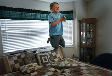 Scott Sommerdorf  |  The Salt Lake Tribune              Six-year-old Logan HIlton jumps on his parents' bed while watching a video in his Eagle Mountain home, Friday July 27, 2012. His mother, Michelle Hilton, qualifies for a new pilot program to treat Logan. The problem is she needs to contribute $6,000 to fully benefit.