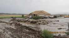 This photo tweeted by the Sanpte County Sheriff's Office shows water swamping a home and lot on July 30, 2012. A thunderstrom dropped water on the area burned in the Wood Hollow Fire.