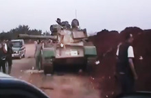 This image made from amateur video released by the Ugarit News and accessed Monday, July 30, 2012, purports to show Free Syrian Army soldiers standing near a military tank in Anadan 16 kilometers (10 miles), from Aleppo, Syria. Syrian government forces mounted new ground attacks against rebel-controlled neighborhoods in Syria's commercial hub of Aleppo, the state media said Monday, July 30, but failed to dislodge the opposition from their strongholds, according to activists. (AP Photo/Ugarit News via AP video) THE ASSOCIATED PRESS IS UNABLE TO INDEPENDENTLY VERIFY THE AUTHENTICITY, CONTENT, LOCATION OR DATE OF THIS HANDOUT PHOTO