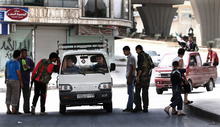In this Sunday, July 29, 2012 photo, Free Syrian Army soldiers are seen at a checkpoint at the border town of Azaz, some 20 miles (32 kilometers) north of Aleppo, Syria. The U.N. said 200,000 Syrians have fled the embattled city of Aleppo since intense clashes between regime forces and rebels began 10 days ago. The government forces turned mortars, tank and helicopter gunships against rebel positions on Monday, July 30, 2012. (AP Photo/Turkpix)