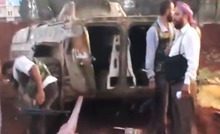 This image made from amateur video released by the Ugarit News and accessed Monday, July 30, 2012, purports to show Free Syrian Army soldiers standing near a destroyed vehicle in 16 kilometers (10 miles), from Aleppo, Syria. Syrian government forces mounted new ground attacks against rebel-controlled neighborhoods in Syria's commercial hub of Aleppo, the state media said Monday, July 30, but failed to dislodge the opposition from their strongholds, according to activists. (AP Photo/Ugarit News via AP video) THE ASSOCIATED PRESS IS UNABLE TO INDEPENDENTLY VERIFY THE AUTHENTICITY, CONTENT, LOCATION OR DATE OF THIS HANDOUT PHOTO