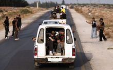 In this Sunday, July 29, 2012 photo, Free Syrian Army soldiers are seen in vehicles at the border town of Azaz, some 20 miles (32 kilometers) north of Aleppo, Syria. The U.N. said 200,000 Syrians have fled the embattled city of Aleppo since intense clashes between regime forces and rebels began 10 days ago. The government forces turned mortars, tank and helicopter gunships against rebel positions on Monday, July 30, 2012. (AP Photo/Turkpix)