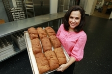In this Thursday, July 14, 2012 photo, Michele Kelly, owner of Pure Knead bakery, poses with a rack of freshly baked gluten-free sandwich bread in Decatur, Ga. A research team led by the Mayo Clinic's Dr. Joseph Murray looked at blood samples taken from Americans in the 1950s and compared them to samples taken from people today, and determined Celiac disease, triggered by gluten, has been increasing, confirming estimates that about 1 percent of U.S. adults have it today, Murray and his colleagues reported Tuesday, July 31, 2012. (AP Photo/John Bazemore)