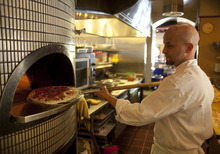 In this photo taken Thursday, July 12, 2012, chef Damon Hall puts a pepperoni pizza into an oven at MoMo's restaurant in San Francisco. With a wood-burning oven at MoMo's, Hall can more than banish the ghosts of pizzas past with a pepperoni pizza that starts with a freshly made crust and is topped with tomatoes, fresh, and cheese, not antique, with oregano, red pepper flakes and other seasonings to kick up the taste. (AP Photo/Eric Risberg)