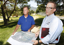 Al Hartmann  |  The Salt Lake Tribune   Parleys Trail project manager Walt Gilmore, left, and Salt Lake County Parks spokesman Martin Jensen look over an aerial map of Sugar House Park where the route is planned. The trail enters the park behind them at 1700 East near Interstate 80, where its design required fill dirt to modify a steep slope and the removal of 30 trees.