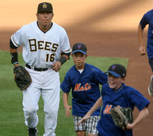 Steve Griffin | The Salt Lake Tribune   Members of a Lehi, Utah junior baseball team race off the field with Bees first baseman Efren Navarro after the National Anthem before game between the Bees and the New Orleans Zephyrs at Spring Mobile Ballpark in Salt Lake City, Utah Wednesday August 1, 2012. The younger players got to take the field with the big league players during introductions.