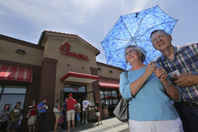 Don and Brenda Nichols shield themselves from 100 degree temperatures as they stand in line for a Chick-fil-a meal at the chain's restaurant in Wichita, Kan., on Wednesday. Aug. 1, 2012. Over 200 people waited in line to buy a meal to show their support for the company that's currently embroiled in a controversy over same-sex marriage.   Former Arkansas Gov. Mike Huckabee, a Baptist minister, declared Wednesday national