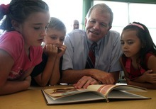 Rick Egan    The Salt Lake Tribune   Jim Smith reads to second Graders, Kiana Turner, Carson Gilchrist, and Jordyn Felix, at Foxboro Elementary, in North Salt Lake, Tuesday, July 31, 2012.  Gov. Herbert and leaders of Prosperity 2020 announced an initiative to get more business volunteers in schools.