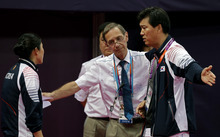 Head badminton referee Torsten Berg, second from right, talks to South Korea's head badminton coach Sung Han-kook, right, after Berg issued a black card to the players in the women's doubles badminton match between South Korea's Ha Jung-eun and Kim Min-jung, and Indonesia's Meiliana Jauhari and Greysia Polii at the 2012 Summer Olympics, Tuesday, July 31, 2012, in London. At left is an unidentified South Korean coach. (AP Photo/Andres Leighton)