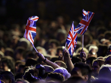 Fans wave British flags during the Opening Ceremony at the 2012 Summer Olympics, Friday, July 27, 2012, in London. (AP Photo/Matt Slocum)