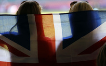 Two fans hold a flag in support of Britain's Olympic team before the start of the women's group E soccer match between New Zealand and Brazil, at the Millennium stadium in Cardiff, Wales, at the 2012 London Summer Olympics, Saturday, July 28, 2012. (AP Photo/Luca Bruno)