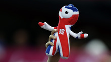 A supporter lifts the Olympic Games 2012 mascot prior to the men's handball preliminary match at the 2012 Summer Olympics, Sunday, July 29, 2012, in London. (AP Photo/Matthias Schrader)