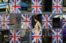 A commuter, seen reflected in the glass of a pub window covered in British flags, walks to work ahead of the 2012 Summer Olympics, Monday, July 23, 2012, in London. (AP Photo/Ben Curtis)