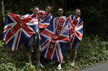 Fans cheer on cyclists as they ride along the path at Box Hill during the Men's Road Cycling race at the 2012 Summer Olympics, Saturday, July 28, 2012, in London. Alexander Vinokourov of Kazakhstan won the gold medal as Rigoberto Uran of Colombia took the silver and Alexander Kristoff of Norway claimed bronze. (AP Photo/Lefteris Pitarakis)