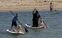 Francisco Kjolseth  |  The Salt Lake Tribune Rob Bolding, center, with Red Mountain Outfitters in St. George takes his daughter Erika, 6, for a demo spin as his son Seth, 11, gets a ride from friend Jake Everett, 10, as the Open Air Demo Day takes to the water kicking off the Outdoor Retailer Summer Market at Jordanelle State Park on Wednesday, August 1, 2012. More than 150 outdoor brands and many more retailers are at the reservoir to show off and experience first-hand the new gear coming out for the summer of 2013. More than 27,000 are expected to attend the twice a year convention held at the Salt Palace Convention Center which runs Aug. 2-5.