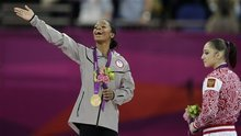 U.S. gymnast Gabrielle Douglas, left, acknowledges the crowd after receiving her gold medal, as Russian gymnast and bronze medallist Aliya Mustafina stands beside her during the artistic gymnastics women's individual all-around competition at the 2012 Summer Olympics, Thursday, Aug. 2, 2012, in London. (AP Photo/Gregory Bull)