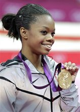 U.S. gymnast Gabrielle Douglas displays her gold medal during the artistic gymnastics women's individual all-around competition at the 2012 Summer Olympics, Thursday, Aug. 2, 2012, in London. (AP Photo/Gregory Bull)