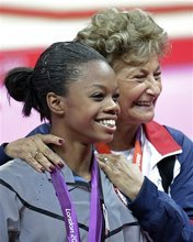 Marta Karolyi, foreground, U.S. national women's gymnastics team coordinator, right, stands with U.S. gymnast and gold medallist Gabrielle Douglas during the artistic gymnastics women's individual all-around competition at the 2012 Summer Olympics, Thursday, Aug. 2, 2012, in London. (AP Photo/Gregory Bull)
