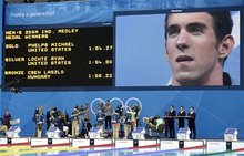 United States' Michael Phelps is seen on a giant display as he listens to the national anthem after receiving his gold medal for the men's 200-meter individual medley swimming final at the Aquatics Centre in the Olympic Park during the 2012 Summer Olympics in London, Thursday, Aug. 2, 2012. (AP Photo/Lee Jin-man)