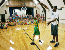 Steve Griffin | The Salt Lake Tribune   Dawson Allred, 10, tries in vane, to shoot over Utah Jazz forward, Derrick Favors, during the Jazz player's visit to Tabiona, Utah and their Junior Jazz program Monday July 30, 2012.
