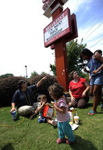 Tascha Madaffari, left, with her children William and Emerson, front, join gay rights supporters Laura Whitman and Taylor Pasqualetti, right, for a picnic outside the Decatur, Ga., Chick-fil-A restaurant Friday, Aug. 3, 2012. Gay rights activists plan kiss demonstrations at Chick-fil-A stores Friday, just days after the company set a sales record when customers flocked to the restaurants to show support for the fast-food chain owner's opposition to gay marriage. (AP Photo/David Tulis)