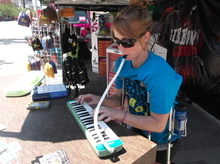 Libby Sauter plays a Melodica at the Gibbon Slacklines booth, in front of the Salt Palace during the Outdoor Retailers Summer Market. The instrument, she says, offers