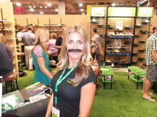 Angie Tate of Carlsbad, Calif., models an official Donovan Frankenreiter mustache at the Sanük booth at the Outdoor Retailer Summer Market. Frankenreiter, the musician and surfer, is a spokesman for the shoe maker. (Photo by Sean P. Means  |  The Salt Lake Tribune)