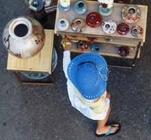Trent Nelson  |  The Salt Lake City Thousands of people were on Main Street for the Kimball Arts Festival in Park City, Utah Friday, August 3, 2012. A young woman in a blue hat looks at Brad Henry's pottery.