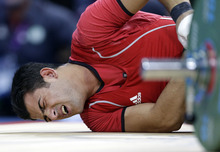 Safaa Al-Jumaili of Iraq lies on the mat injured after competing during the men's 85-kg, group B, weightlifting competition at the 2012 Summer Olympics, Friday, Aug. 3, 2012, in London. (AP Photo/Hassan Ammar)